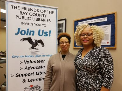 Image of people standing in front of wall in a building with a Friends of the Bay County Libraries sign off to the side