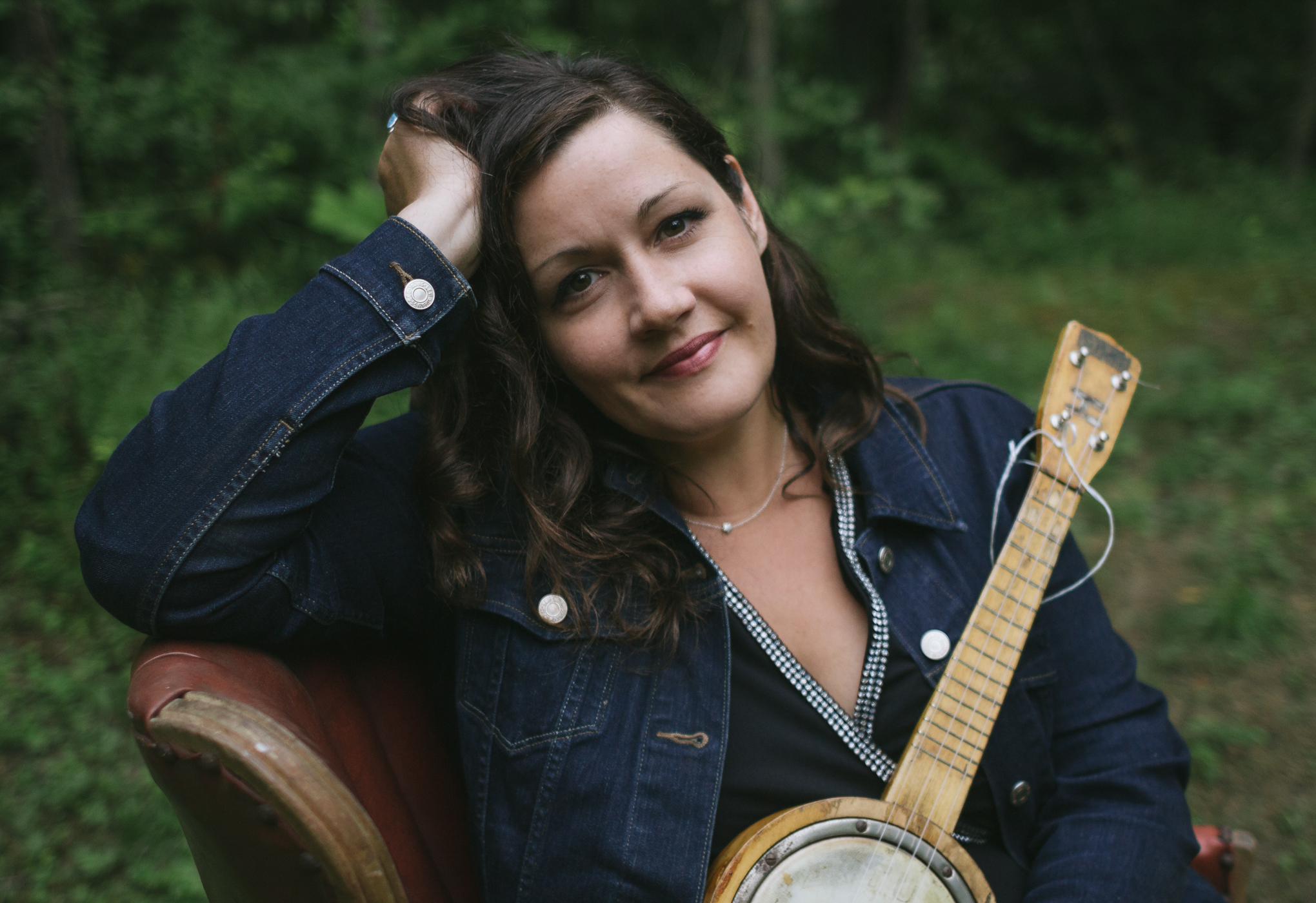 Photo of posed woman with light skin and long dark hair holding a banjo