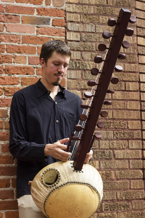 Photo of musician Sean Gaskell holding Kora and standing in front of brick wall
