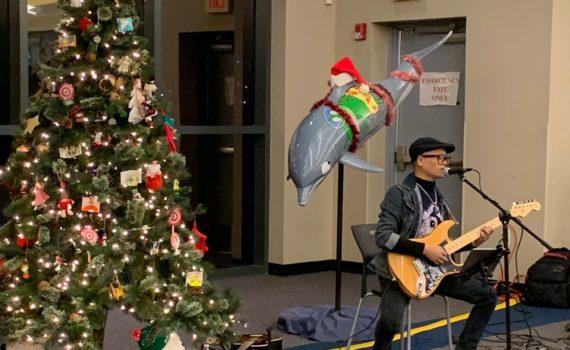 Photo of Ashesh Dangol playing guitar near decorated Christmas tree